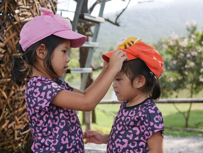 Portrait of girls wearing cap standing outdoors
