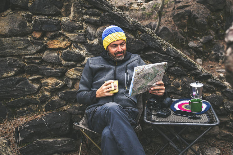 Bearded middle-aged man with woolen hood resting sitting after a trekking day Male drinking coffee looking on the map. Relaxing with hot beverage in the National Park. Positive and healthy concept One Person Real People Clothing Lifestyles Front View Winter Sitting Warm Clothing Three Quarter Length Young Adult Leisure Activity Holding Cold Temperature Mug Solid Portrait Adult Technology Rock - Object Outdoors