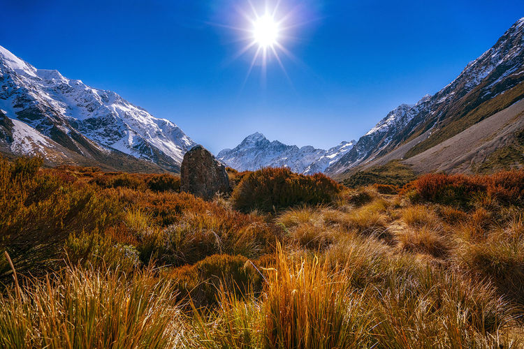 Clear blue skies while trekking in Aoraki Mount Cook National Park. Aoraki Mount Cook National Park Sunburst Beauty In Nature Cold Temperature Day Grass Landscape Mountain Mountain Range Nature No People Outdoors Scenics Sky Snow Sun Sunlight Tranquil Scene Tranquility Vegetation Winter