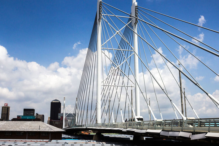Low Angle View Of Nelson Mandela Bridge Against Cloudy Sky On Sunny Day