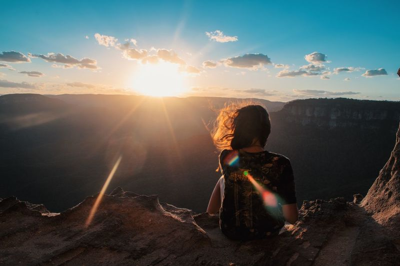 Bright future ahead Sky One Person Child Childhood Sunset Nature Sitting Leisure Activity Sunlight Cloud - Sky Offspring Land Rear View Beauty In Nature Sun Real People Lifestyles Women Outdoors