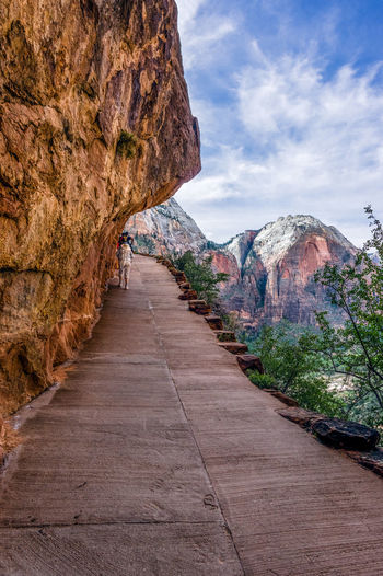 Walkway amidst rock formation against sky