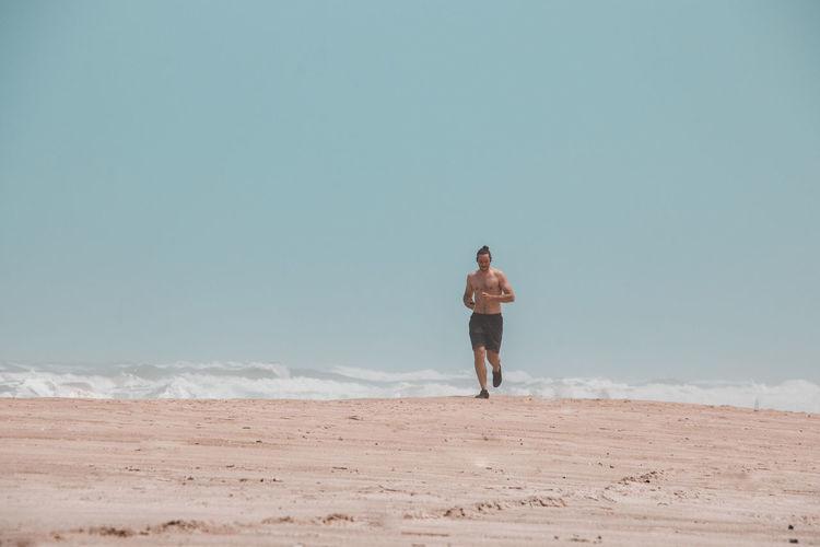 Shirtless man running at beach against sky