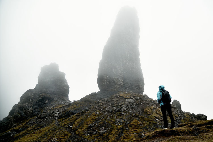 Low angle view of female hiker standing on mountain during foggy weather