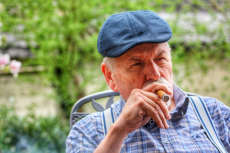 Senior Man Smoking Cigar While Sitting In Yard