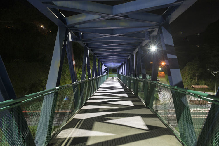 Deserted pedestrian overpass at night in Petropolis - interior city of Rio de Janeiro, Brazil Direction The Way Forward Architecture Diminishing Perspective Built Structure Illuminated Bridge Shadow Railing Nature No People Sunlight Bridge - Man Made Structure Connection Transportation Footbridge Outdoors Footpath vanishing point Long