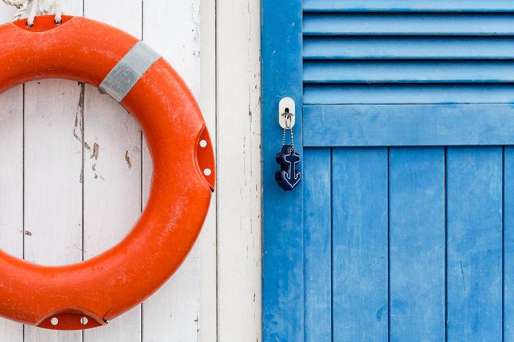 Life belt hanging on closed wooden door