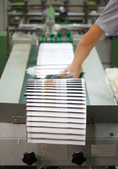 Stack of books with worker working at production line in factory