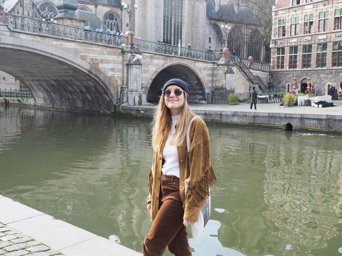 Young woman standing by canal against bridge