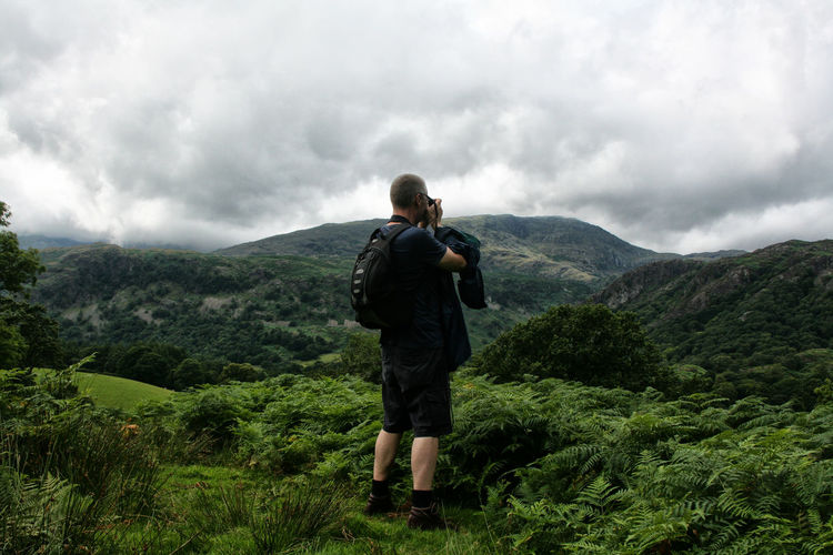 Rear view of man standing on mountain against distant mountains and sky in peak district, england