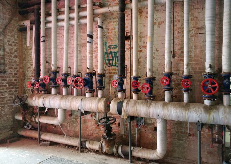 Pipes against brick wall in industry