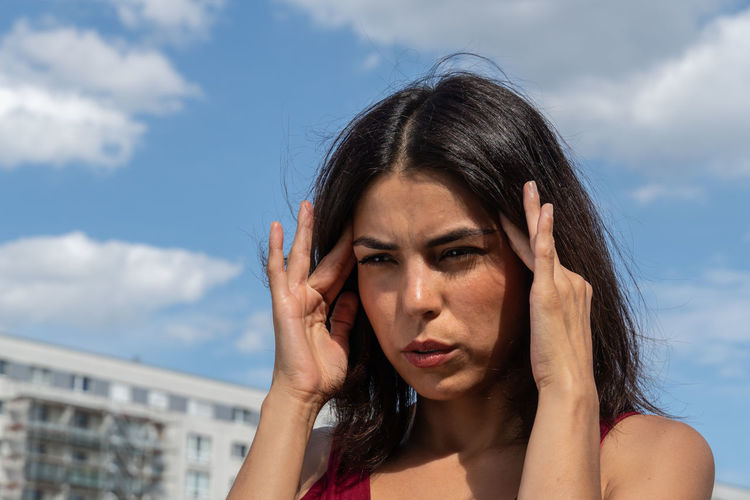 Woman touching forehead in pain against sky