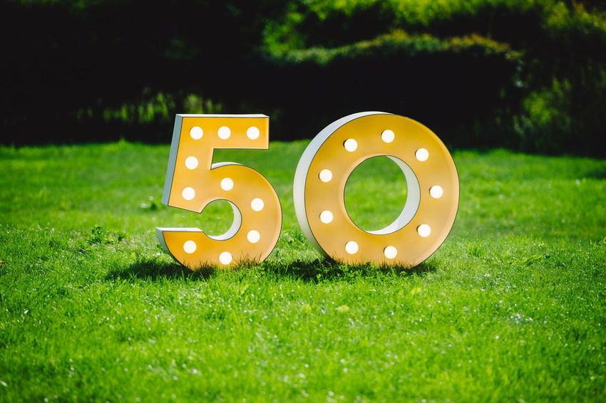 Illuminated decorated number letters symbolising 50th anniversary standing on green field surrounding by dark trees on a sunny day 50th 50th Birthday Happy Anniversary Arts Culture And Entertainment Decoration Field Fifty Grass Green Color Illuminated Land Lawn Metallic Nature No People Number Outdoors Park Park - Man Made Space Plant Selective Focus Shape Year