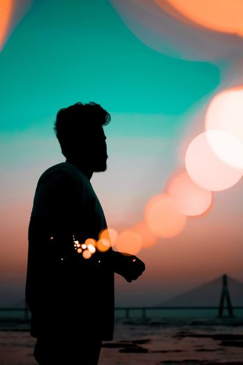 Silhouette man standing against defocused light during sunset