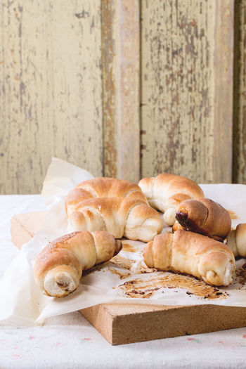 Fresh homemade baked crescent rolls on baking paper and oven stone over Baked Bakery Baking Paper Bread Bread Rolls Bun Crescent Food French Food Fresh Baked Bread Homemade Bread Homemade Food Rolls Stone Sugar Table Tablecloth White