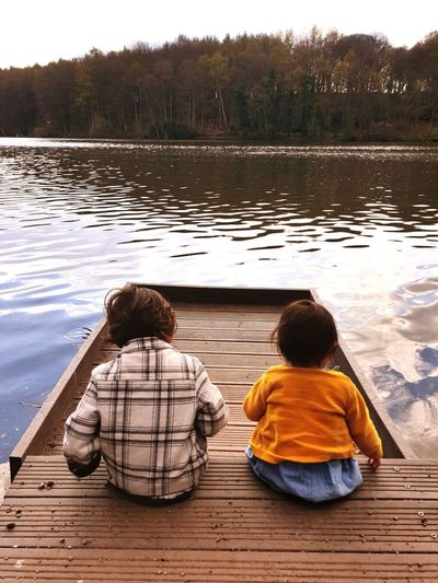 Rear view of siblings sitting on pier over lake