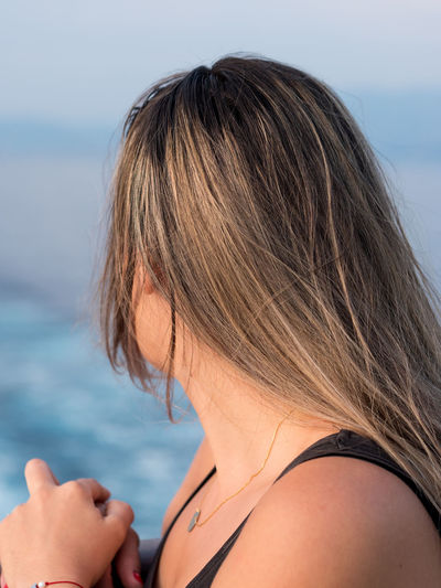 Close-up of woman looking at sea against sky