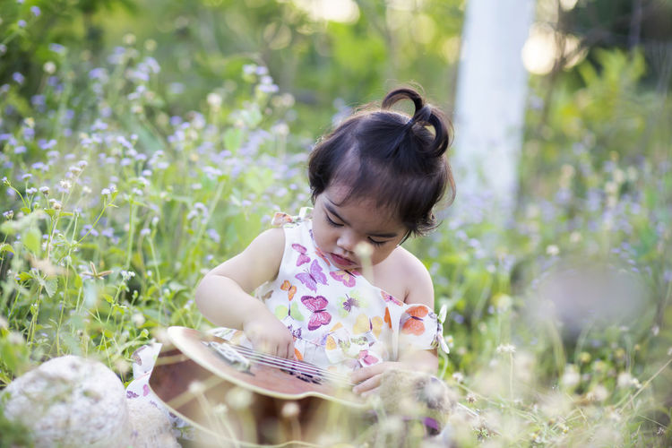 Rear view of girl looking at flowering plants