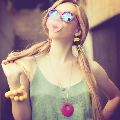 Close-up of beautiful young woman blowing bubble gum