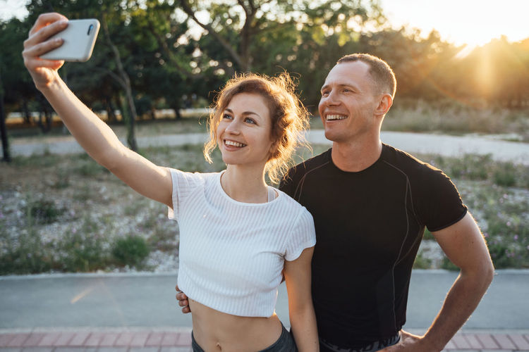 Couple taking selfie on smart phone at park