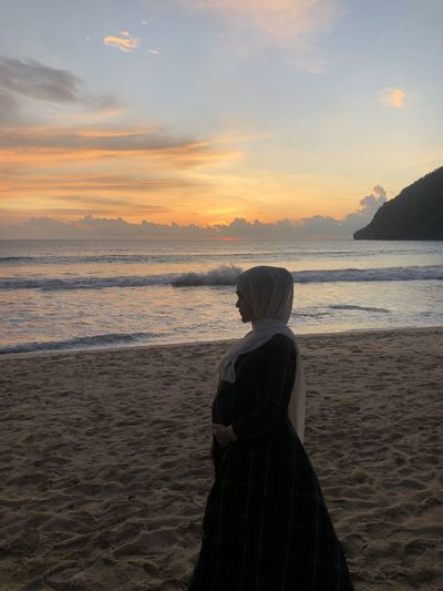 Side view of woman in hijab looking away while standing at beach
