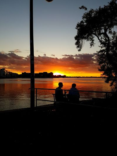 Silhouette men sitting by lake against sky during sunset