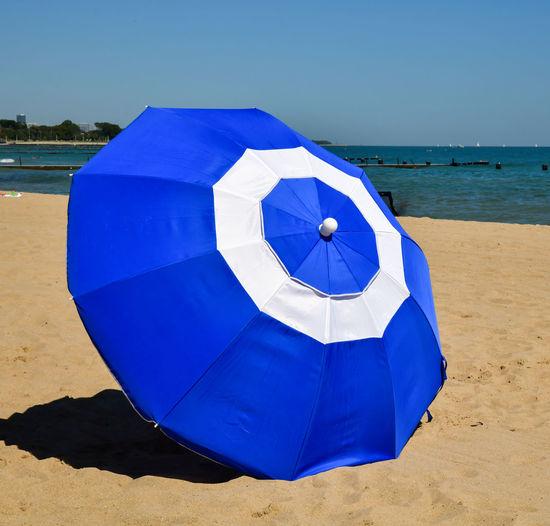 Blue umbrella on beach against clear sky