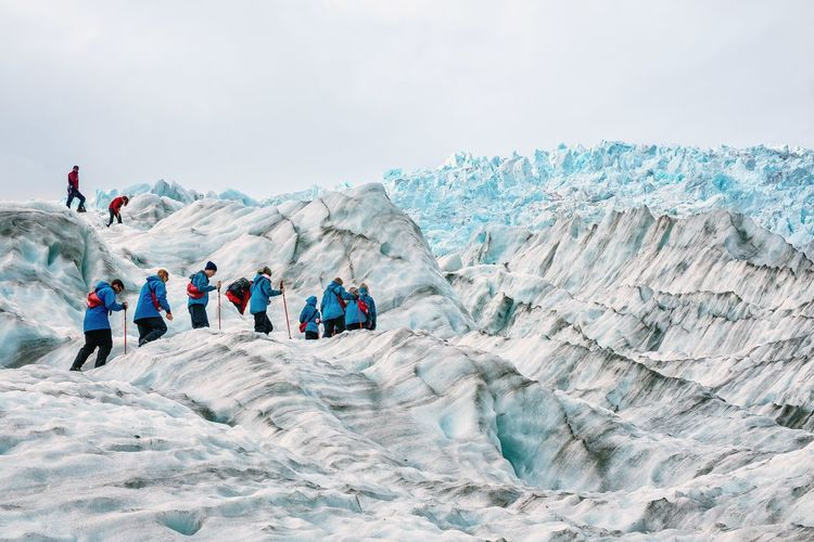 People Walking On Glaciers Against Sky
