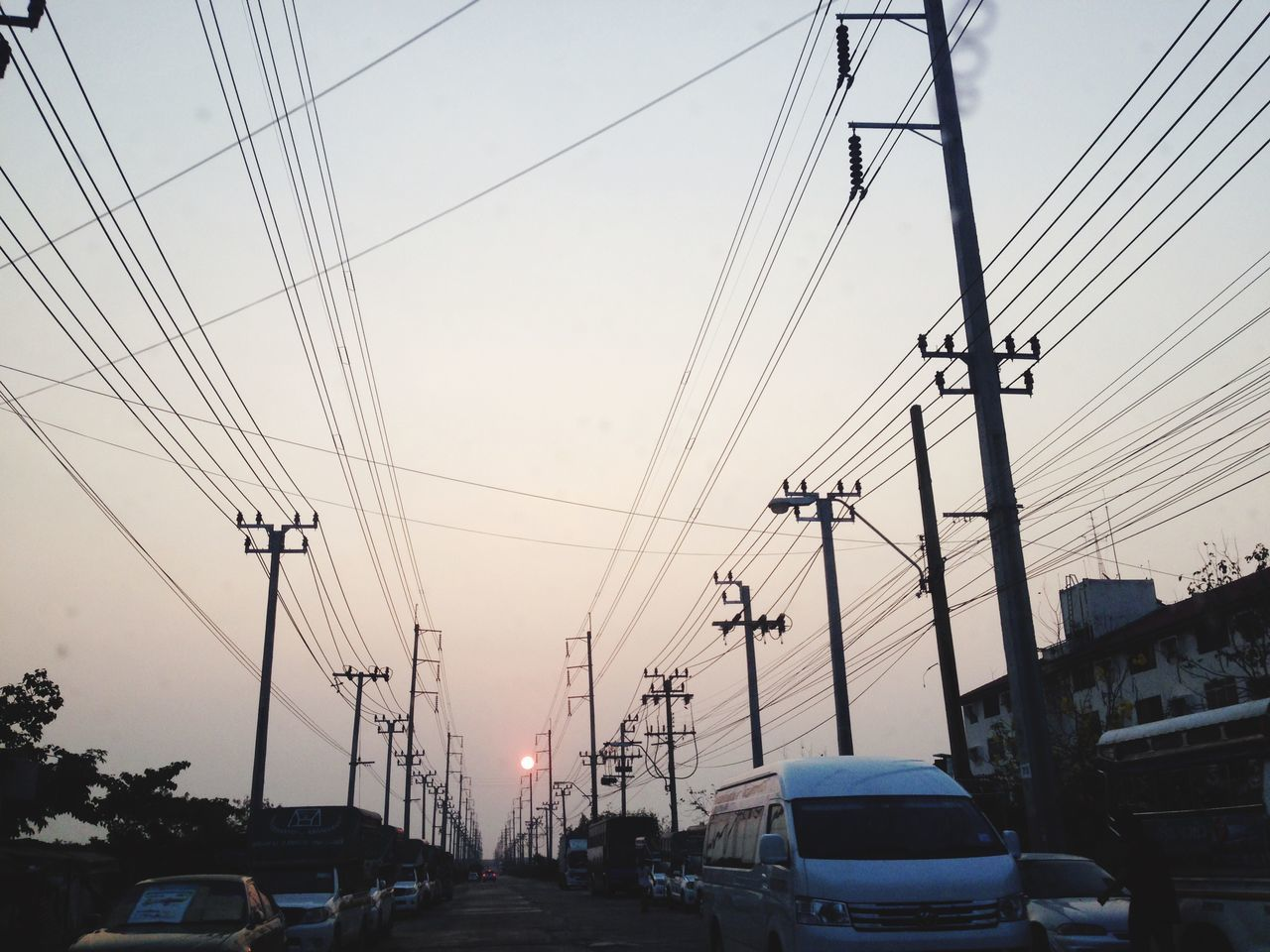 mode of transportation, cable, electricity, sky, transportation, motor vehicle, car, power line, technology, land vehicle, electricity pylon, architecture, connection, power supply, sunset, nature, city, no people, built structure, street, complexity, outdoors