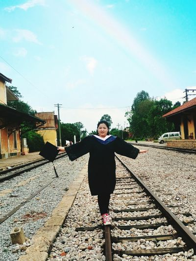 Young Woman In Graduation Gown Walking On Railroad Track Against Sky
