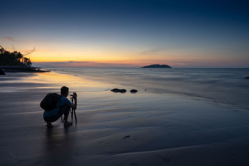 Rear view of man photographing sea at beach against sky during sunset