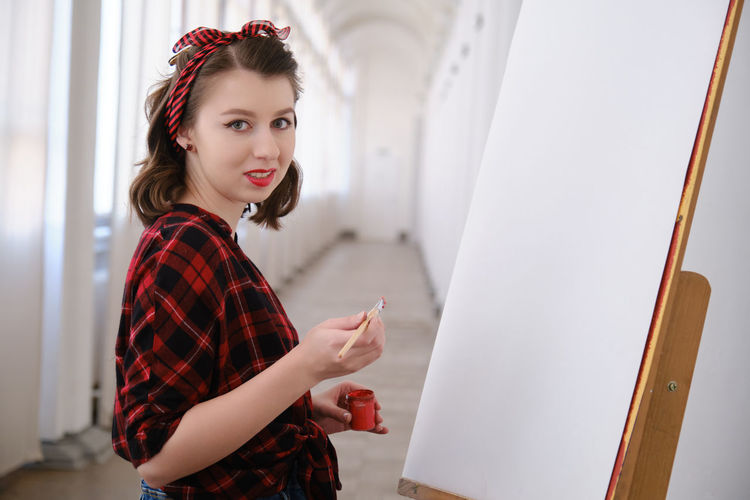 Portrait of beautiful woman standing at home