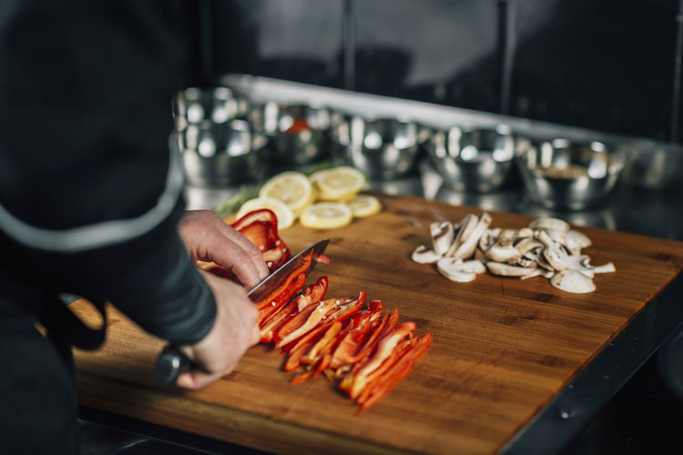 Cooking dinner - chef holding a knife and cutting red bell pepper