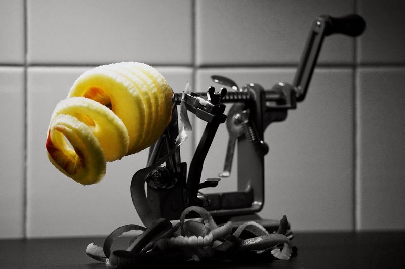 Close-Up Of Apple On Peeler In Kitchen