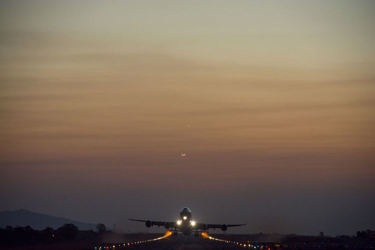 Airplane Flying At Runway Against Sky During Sunset