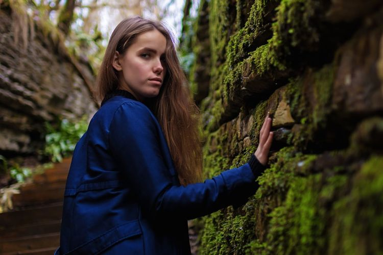 Side view portrait of young woman standing by mossy wall
