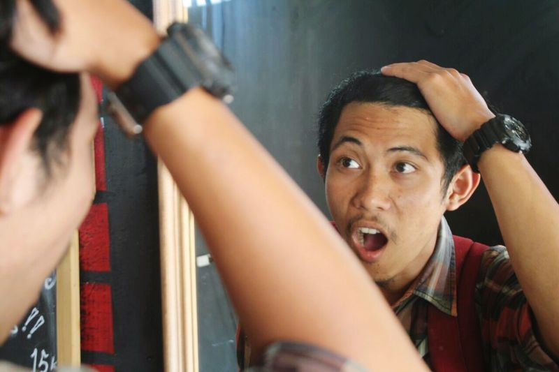 Close-up of shocked young man with reflection on mirror