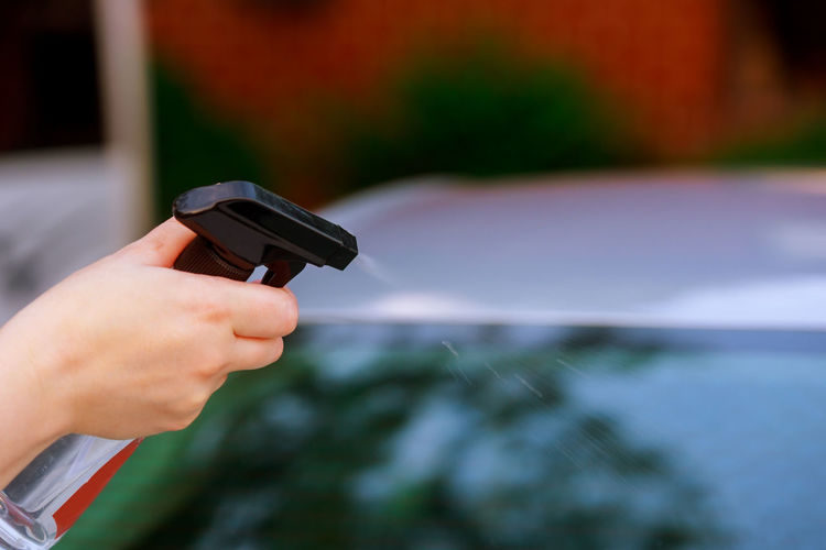 Close-up of person using spray bottle on car