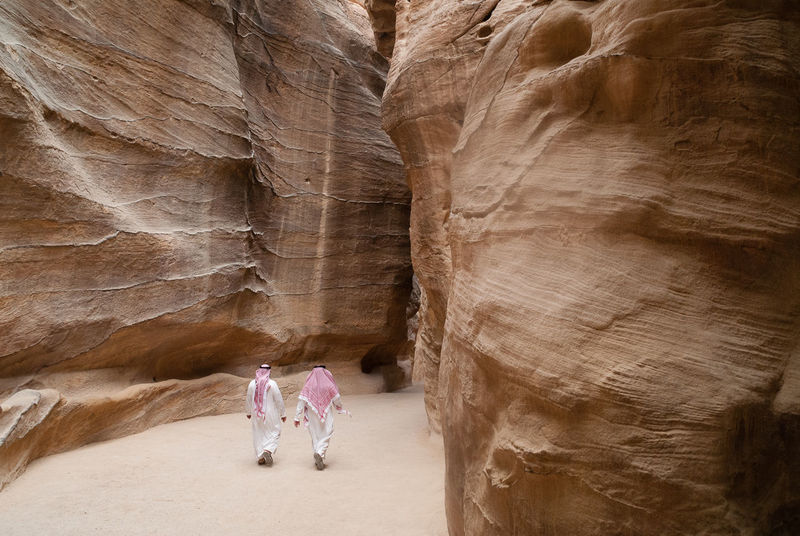 Two Arab tourists walk through the Siq in Petra en route to the Treasury Ancient Arabs Path Petra The Siq Tourists Walk Walking Around Adult Beauty In Nature Carved Day Full Length Geology Indoors  One Person Pathway People Rear View Rock - Object Rock Formation Siq
