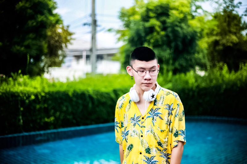 Teenage Boy Wearing Eyeglasses While Standing Against Swimming Pool
