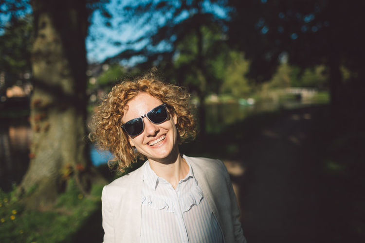 Beautiful Woman Curly Hair Emotion Fashion Focus On Foreground Front View Girl Glasses Hair Hairstyle Happiness Headshot Leisure Activity Lifestyles Looking At Camera Nature One Person Outdoors Portrait Real People Smiling Spring Sunglasses Tree Young Adult