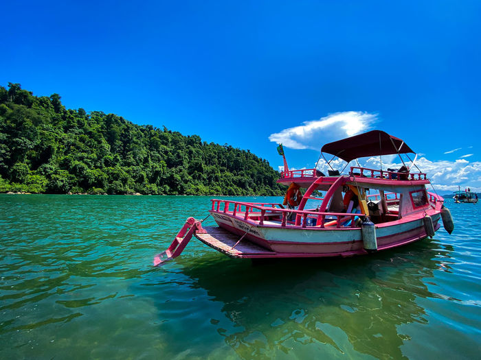 Boat moored in water against blue sky