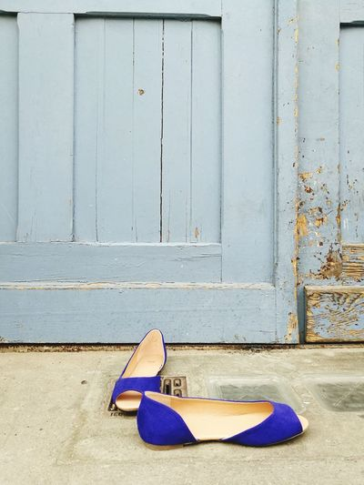 Shoes on closed door of abandoned house
