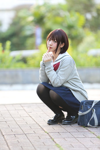 Young Woman In School Uniform Crouching At Park