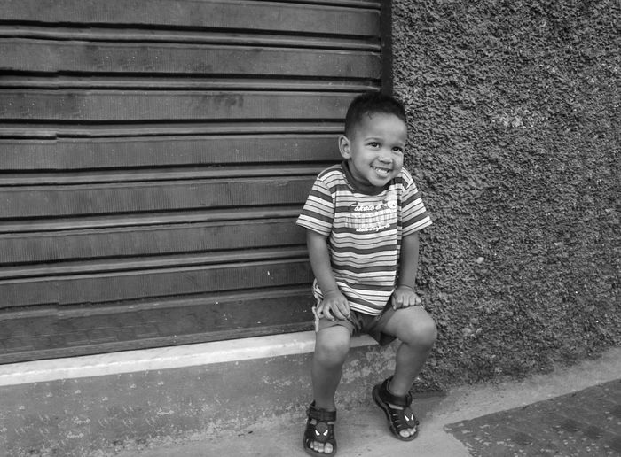 Boy Smiling While Sitting By Closed Shutter