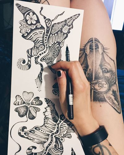 Cropped Image Of Hand Drawing Tattoo Design On Paper