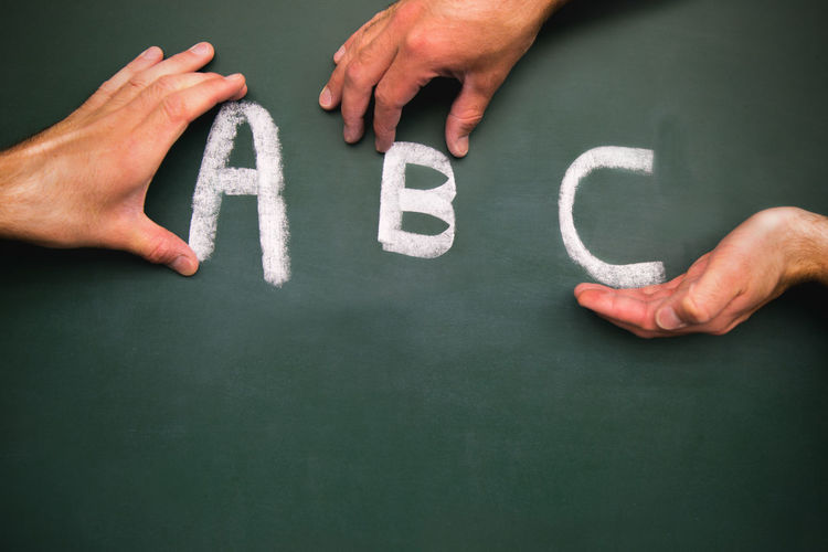 Cropped hands of people touching alphabets on blackboard