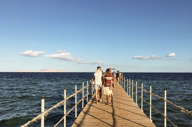 Rear View Of Couple Walking On Pier Over Sea Against Sky