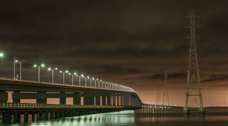 Illuminated San Mateo-Hayward Bridge Over River Against Cloudy Sky At Night
