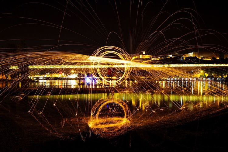 Light trails in river against sky at night
